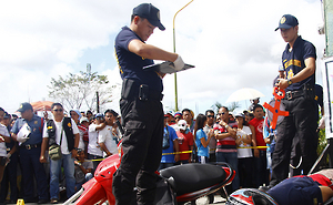 Police officers at the crime scene of the murder of Rogelio Butalid, a broadcast commentator, outside his radio station in Tagum City, in the southern Philippines on December 11, 2013. A witness told Human Rights Watch that a Tagum Death Squad member shot Butalid at point-blank range.