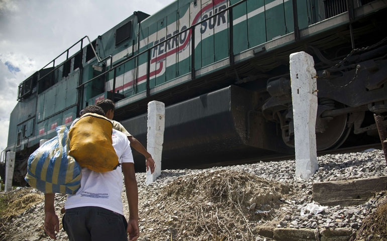 "In Mexico July 22, a Central American migrant walks toward ""La Bestia,"" a cargo train headed for the U.S. border. (Newscom/AFP/Getty Images/Ronaldo Schemidt)"