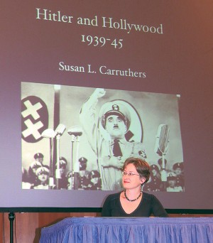 Susan Carruthers, a professor of history at Rutgers-Newark, seated below a poster for The Great Dictator, Charlie Chaplin's satirical 1940 film portrait of Adolf Hitler. Carruthers said the Production Code, which laid out strict regulations of what could and could not be shown in Hollywood movies, prevented any Hollywood-produced anti-Nazi films until 1939.
